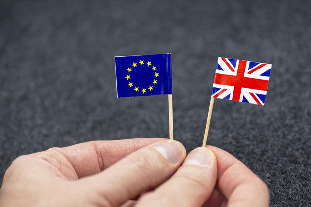 Man holding small paper flags of eu and great britain as symbol of brexit, concept picture Premium Photo